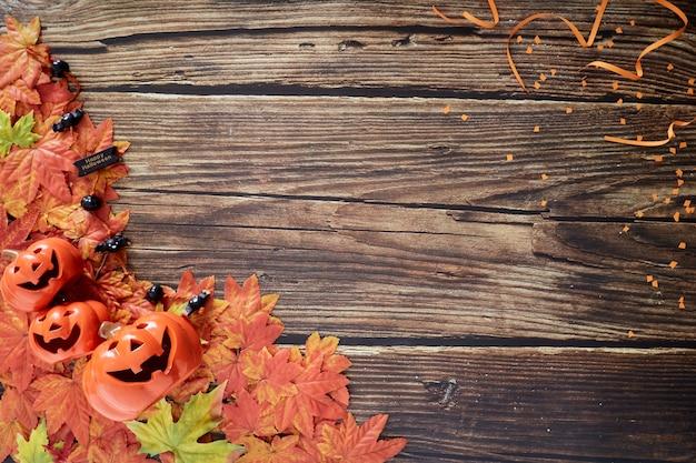Citrouilles d'halloween avec des feuilles d'automne d'automne sur bois