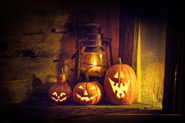 Citrouilles d'halloween et lanterne dans une vieille maison près de la fenêtre où brille le clair de lune.