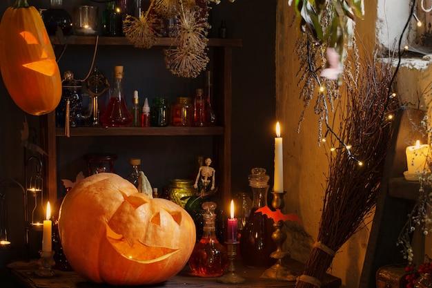 Citrouilles d'halloween avec des lumières et des bougies allumées et des potions magiques dans la maison de la sorcière