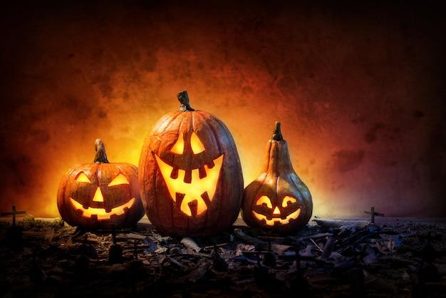 Citrouilles d'halloween sur les ruines et les tombes effrayantes la nuit.