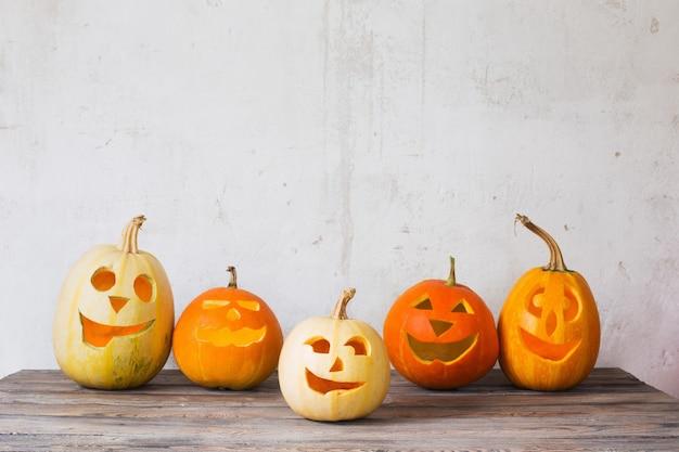 Citrouilles d'halloween sur table en bois sur fond vieux mur blanc