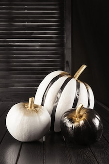 Citrouilles noires et blanches. décoration de la maison pour halloween dans le style moderne. verticale.