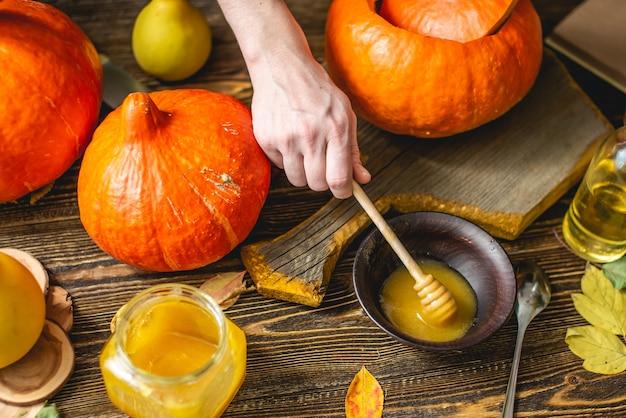 Citrouilles orange pour la cuisson avec du miel et de la cannelle sur fond de table en bois