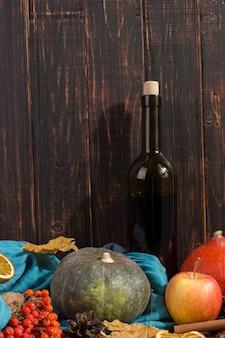 Citrouilles, pommes, écharpe, feuilles sèches et vin, humeur d'automne. fond, surface.