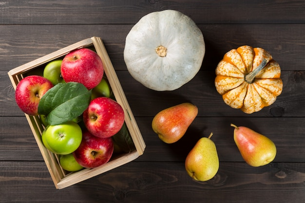 Citrouilles avec des pommes mûres dans une boîte et poires sur bois sombre.