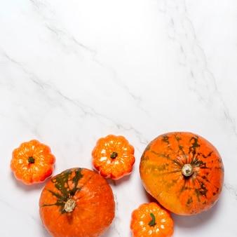 Citrouilles sur surface en marbre. concept halloween, automne, récolte. carré. mise à plat, vue de dessus