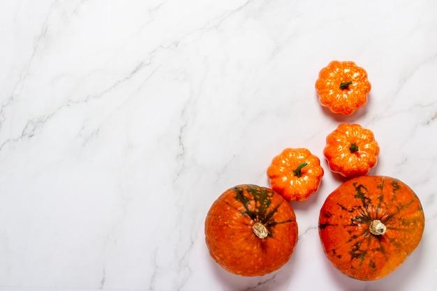 Citrouilles sur surface en marbre. concept halloween, automne, récolte. mise à plat, vue de dessus