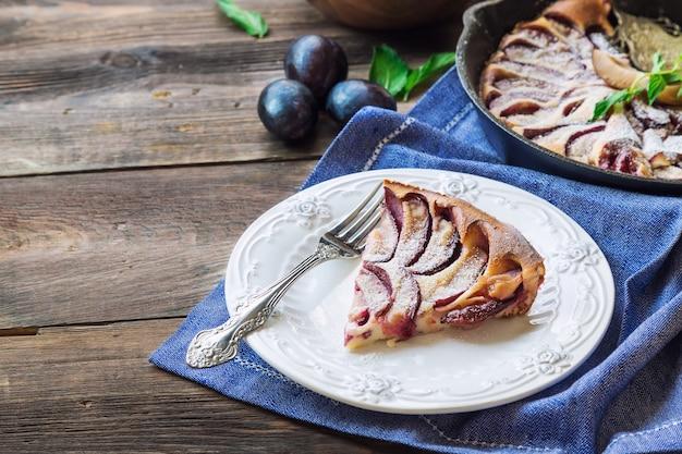 Clafoutis aux prunes fraîches faites dans une poêle en fer sur bois rustique.