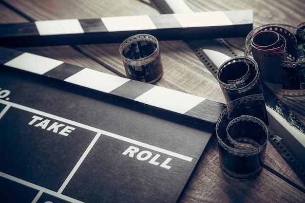 Clap de cinéma et bandes de film sur fond de bois