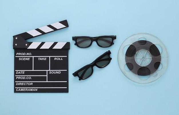 Clap de cinéma, bobine de film et lunettes 3d sur bleu. industrie du divertissement. cinéma