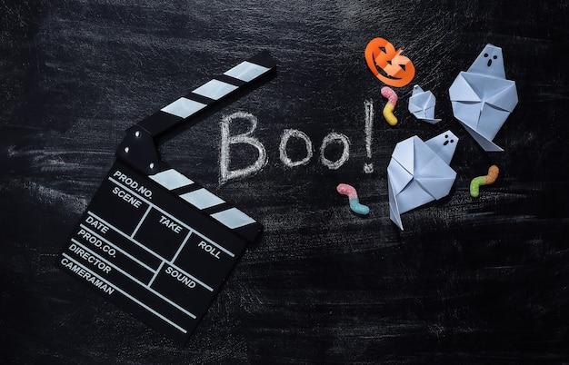 Clap de cinéma et lettrage à la craie boo ! sur un tableau noir avec un décor helloween. thème halloween