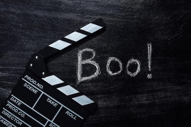 Clap de cinéma et lettrage à la craie boo ! sur un tableau noir. thème halloween
