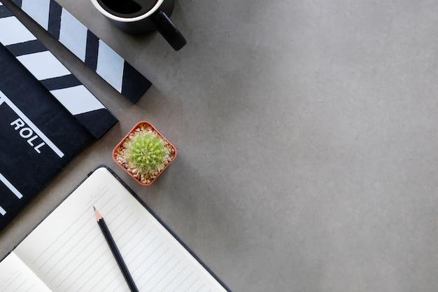 Clap de cinéma avec papier bloc-notes, tasse de café, cactus sur la vue de dessus de table de directeur et espace de copie.