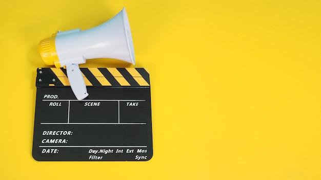 Clap ou clap de cinéma de couleur jaune et noire et mégaphone isolé sur fond jaune. il est utilisé dans la production cinématographique, cinématographique et vidéo.