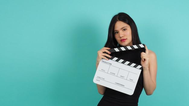 Clap ou clap de film dans la main d'une femme avec une couleur noire. il est utilisé dans la production vidéo, le cinéma, l'industrie du cinéma sur fond vert ou bleu tiffany. elle porte une robe noire