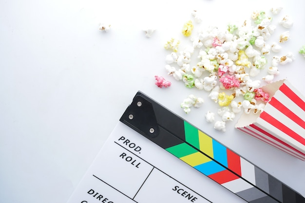 Clap de film et pop-corn sur blanc