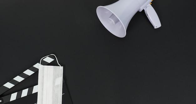 Clap noir ou ardoise de film et masque facial, mégaphone sur fond noir. il est utilisé dans la production vidéo et l'industrie cinématographique.