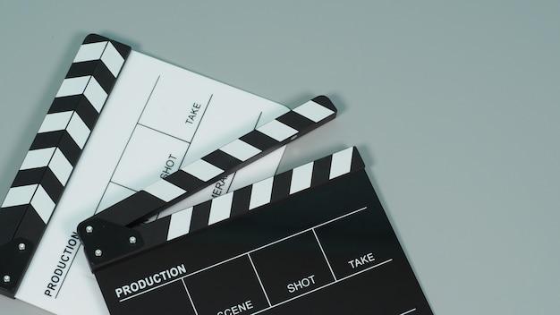 Clap noir et blanc ou clap ou ardoise de film sur fond gris