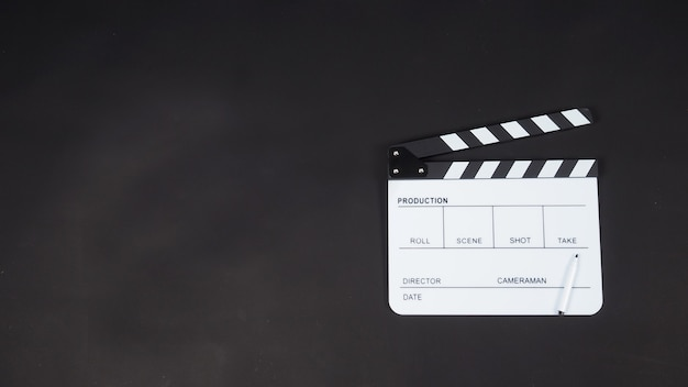 Clap noir ou clap board ou ardoise de film avec utilisation de stylo dans la production vidéo, le cinéma, l'industrie du cinéma. mettez sur fond noir.