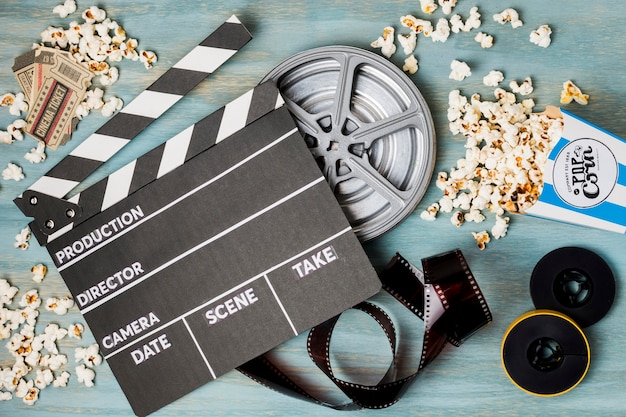 Claperboard; pop corn; bande de film et billets de cinéma sur un bureau en bois
