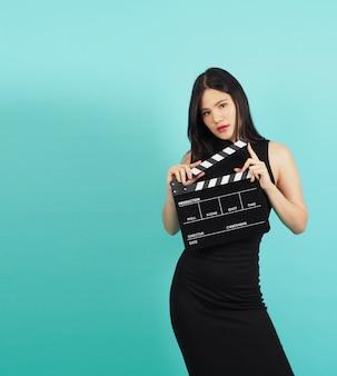 Clapper board ou clap de cinéma chez une adolescente ou une femme hand.it utilisé dans la production vidéo, le cinéma, l'industrie du cinéma sur fond vert ou bleu tiffany. elle porte une robe noire