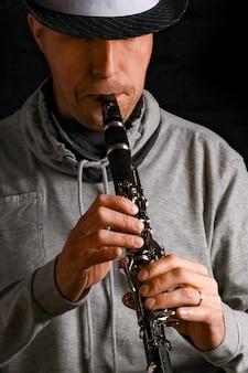 Clarinette entre les mains d'un homme sur une surface noire