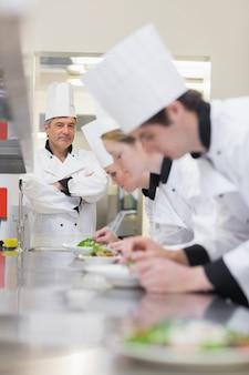 Classe culinaire faisant des salades en tant que professeur supervise