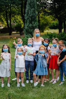 Une classe d'écoliers masqués s'entraîne en plein air pendant l'épidémie. retour à l'école, apprendre pendant la pandémie.