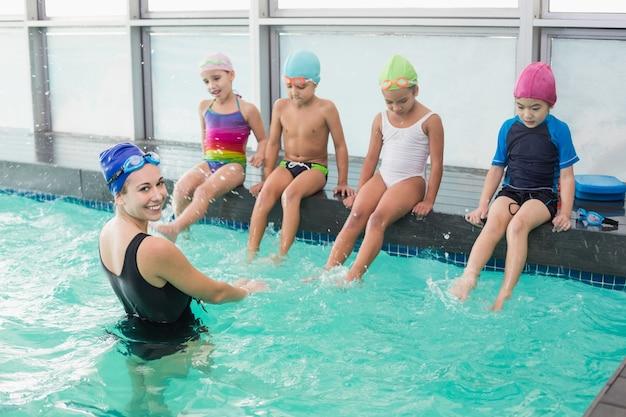 Classe de natation mignonne regardant l'entraîneur