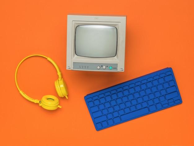 Un clavier bleu, des écouteurs jaunes et un moniteur gris sur fond orange. mise à plat.