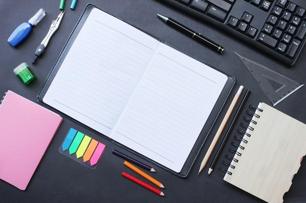 Clavier bloc-notes et crayon avec vue de dessus et accessoires placés sur un bureau noir.