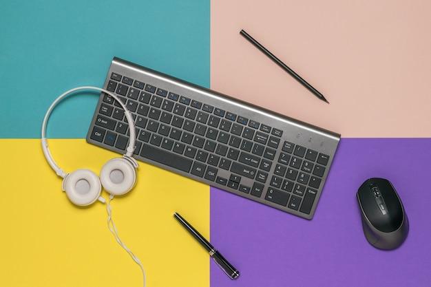 Clavier, crayons, souris et écouteurs sur une surface multicolore. lieu de travail du designer.