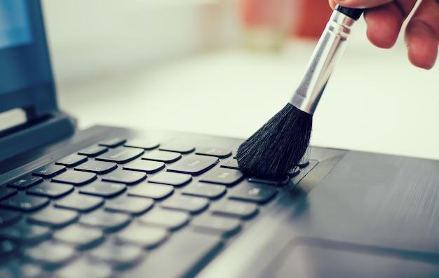 Clavier de nettoyage et ordinateur de soins. main masculine avec une brosse pour enlever la poussière du clavier