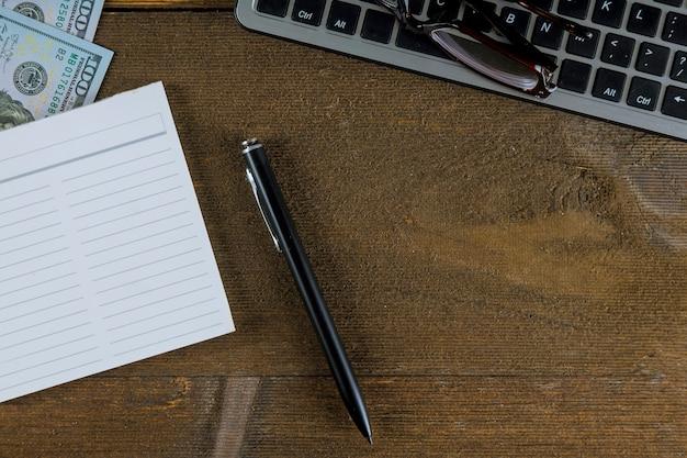 Clavier d'ordinateur pc avec de l'argent en tant que commerce électronique avec stylo et lunettes pour la vision