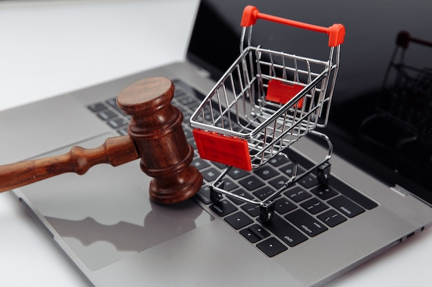 Clavier d'ordinateur portable, caddie et marteau de vente aux enchères sur table, concept de vente aux enchères en ligne.