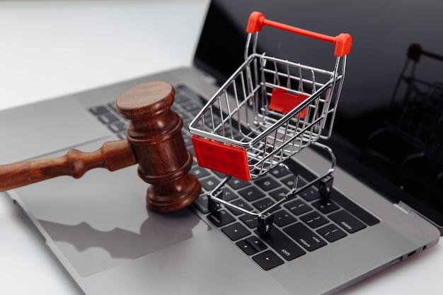 Clavier d'ordinateur portable, panier et marteau de vente aux enchères sur table, concept de vente aux enchères en ligne.