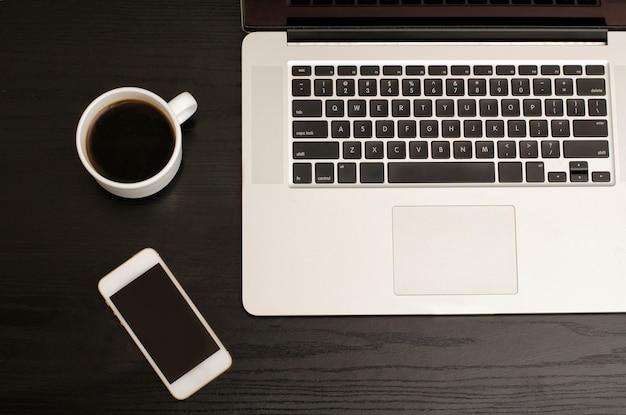 Clavier d'ordinateur portable, téléphone et tasse à café sur une table noire, gros plan