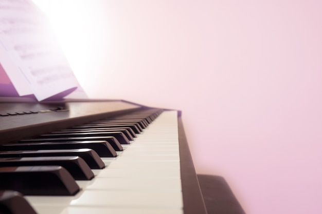 Clavier de piano avec note. filtre de couleur rose avec effet de lumière. copiez l'espace.