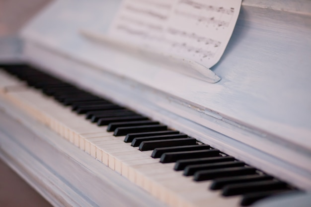 Clavier de piano vintage blanc avec des touches et des partitions en noir et blanc.