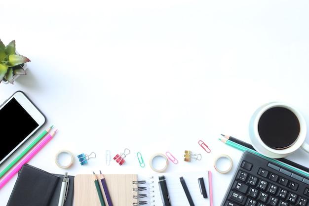 Un clavier, un smartphone, un ordinateur portable, une tasse de café, un stylo et des fournitures sont placés sur un bureau blanc.