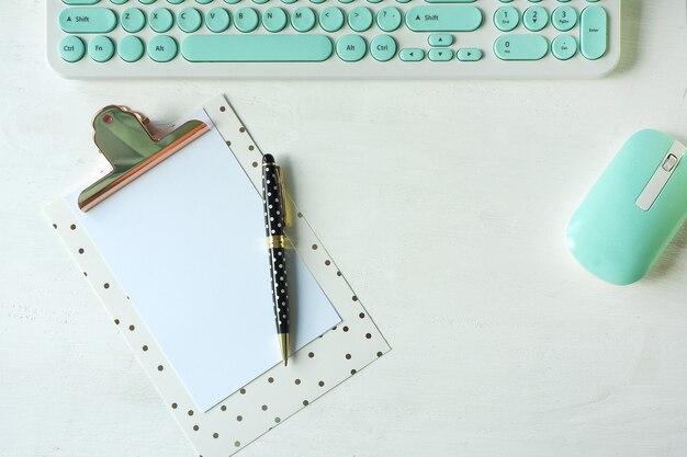 Un clavier et une souris blancs-bleus, un presse-papiers et un stylo blanc à pois noirs.