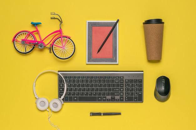 Clavier, souris, écouteurs et accessoires sans fil sur une surface jaune. lieu de travail du designer.