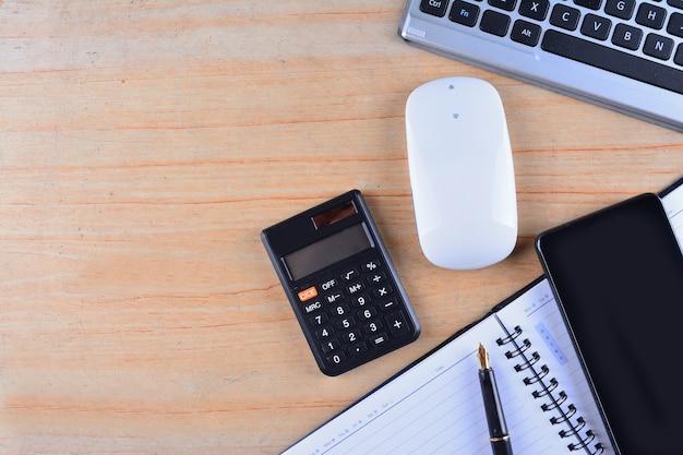 Clavier et souris, stylo plume, bloc-notes, calculatrice et smartphone sur une table