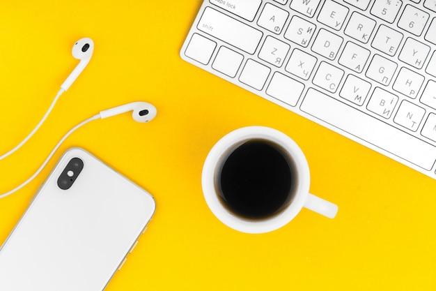 Clavier, téléphone et tasse de café noir.