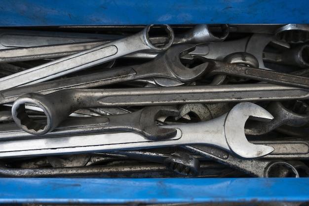 Clé ancienne et sale, clé mixte dans une boîte à outils bleue