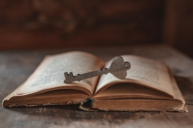 Une clé en bois décorative repose sur un vieux livre vintage ouvert
