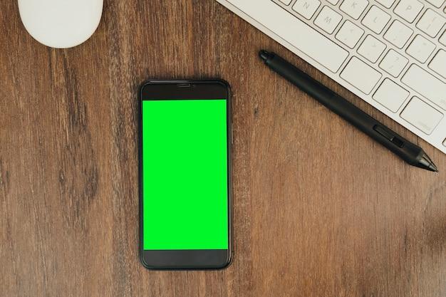 Clé chroma verte sur l'écran du smartphone sur fond de bois avec un ordinateur à côté.
