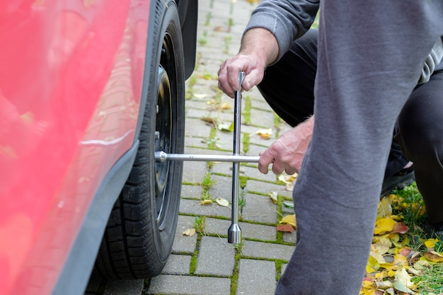 Une clé dans les mains d'un mécanicien automobile dévisse les boulons et les écrous d'un jour d'automne de roue de voiture
