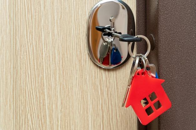 Clé dans la serrure avec porte-clés rouge sous la forme d'une maison