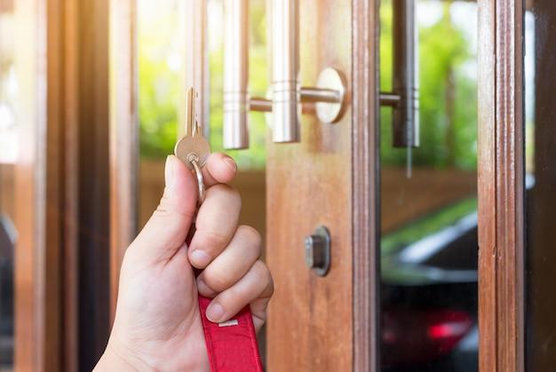 Clé sur la main des gens ouvrent la porte à l'intérieur, porte extérieure ouverte mettant dans la porte d'entrée